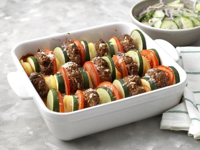 Recept voor ovenschotel van gehakt, courgette en tomaat met komkommersalade