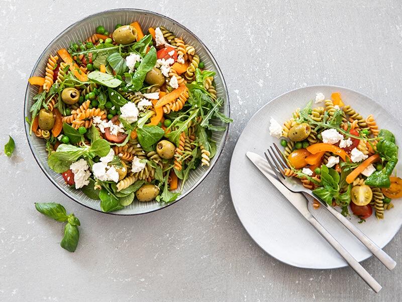 Gekleurde pastasalade met kerstomaatjes, paprika, doperwten en feta