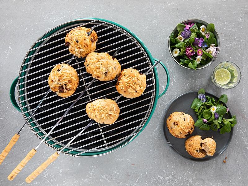 Zelfgemaakte gevulde broodjes van de bbq met olijven, zongedroogde tomaat, kaas en pijnboompitjes